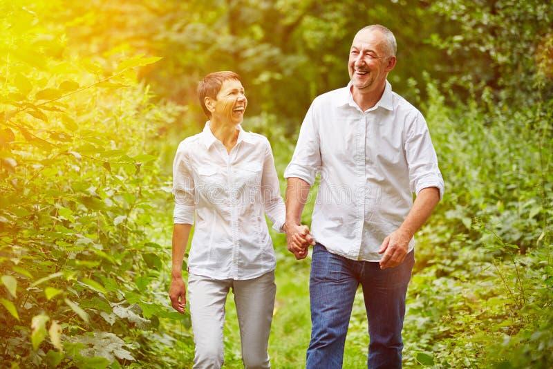 Couples supérieurs heureux faisant le tour en été images stock