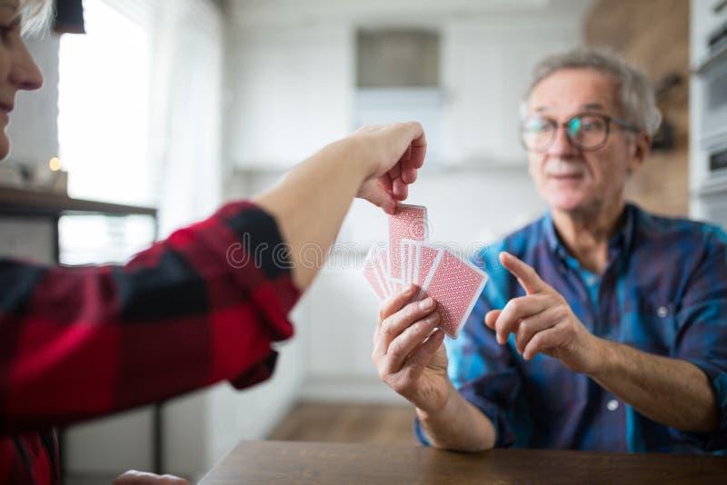 Couples supérieurs heureux jouant des cartes ensemble images stock