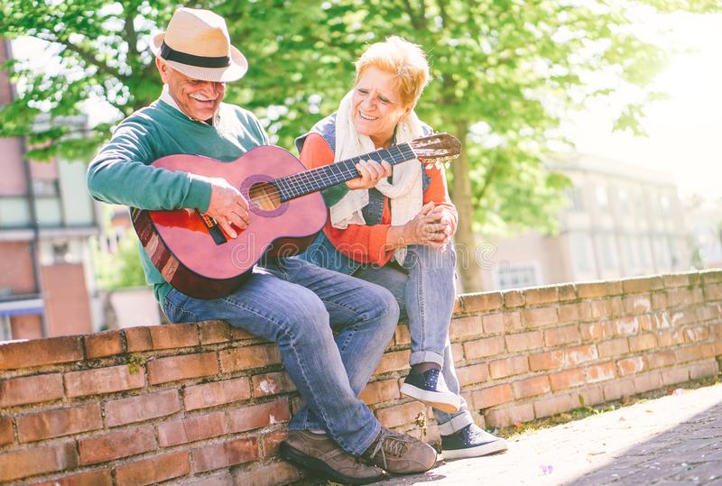 Couples supérieurs heureux jouant une guitare tout en se reposant dehors sur un mur un jour ensoleillé photos libres de droits