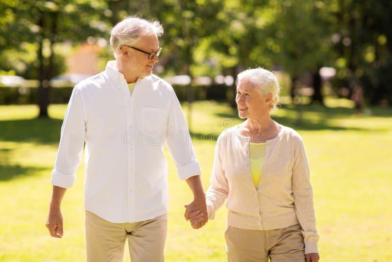 Couples supérieurs heureux marchant au parc d'été photographie stock libre de droits