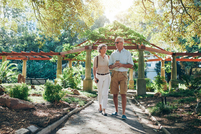Couples supérieurs heureux marchant ensemble en parc de ville photographie stock