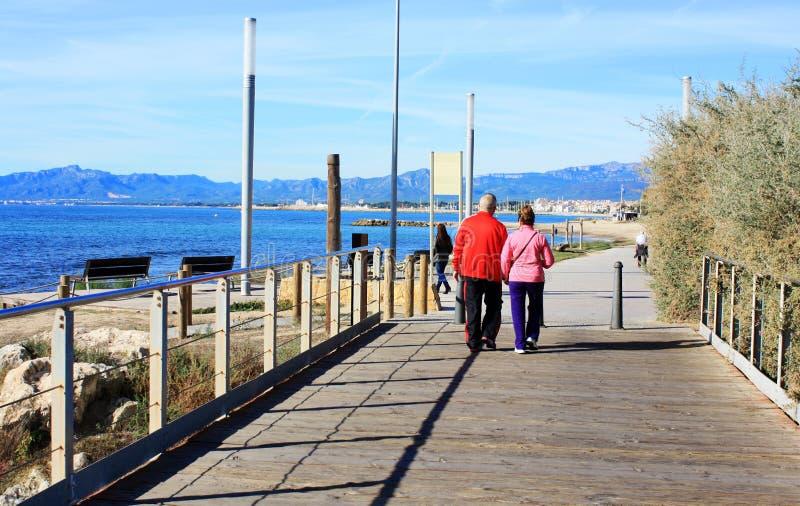 Couples supérieurs heureux marchant le long de la côte la mer de mediteranea image libre de droits