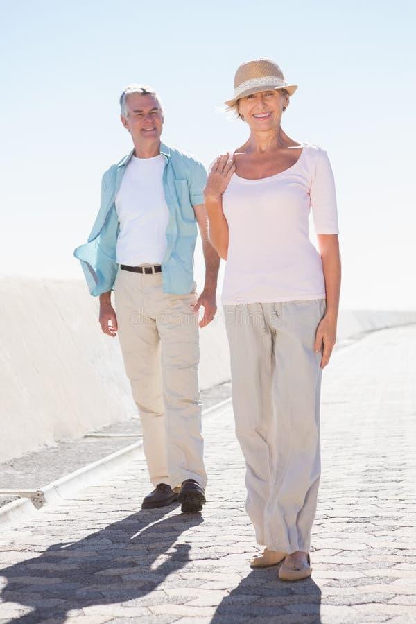 Couples supérieurs heureux marchant sur le pilier image libre de droits