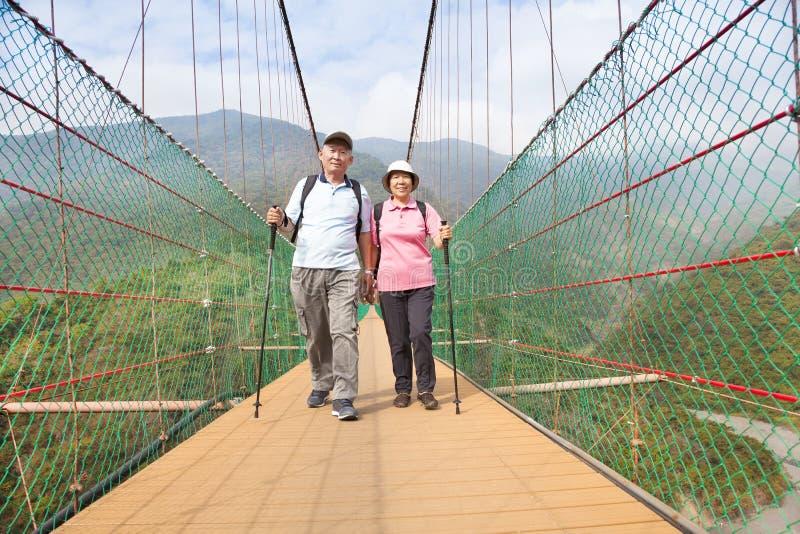 Couples supérieurs heureux marchant sur le pont dans le n images libres de droits