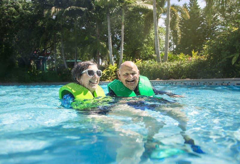 Couples supérieurs heureux nageant ensemble sur une rivière paresseuse images stock