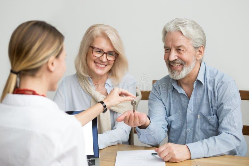 Couples supérieurs heureux obtenant des clés à la nouvelle maison de l'agent immobilier image stock