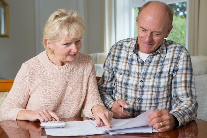 Couples supérieurs heureux passant en revue des finances domestiques ensemble images stock