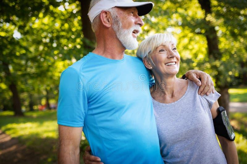 Couples supérieurs heureux restant l'ajustement à côté du fonctionnement de sport images libres de droits