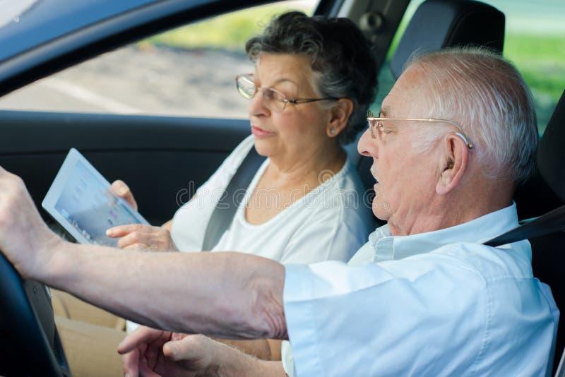 Couples supérieurs heureux se reposant à l'intérieur de la voiture images stock