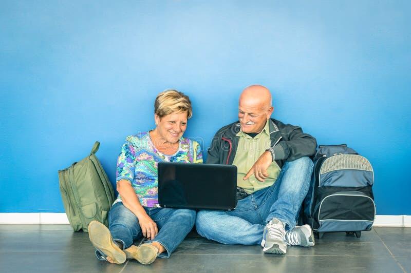 Couples supérieurs heureux se reposant sur le plancher avec l'ordinateur portable à l'aéroport images stock