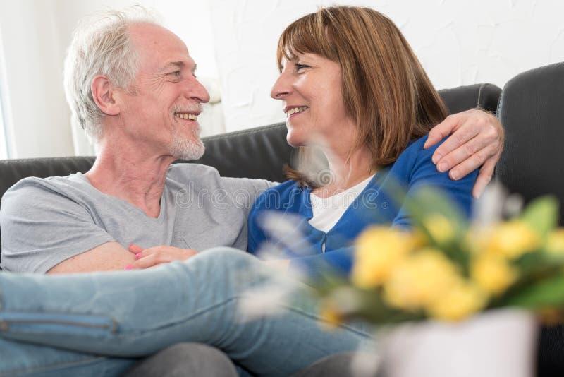 Couples supérieurs heureux se reposant sur le sofa et s'embrassant image stock