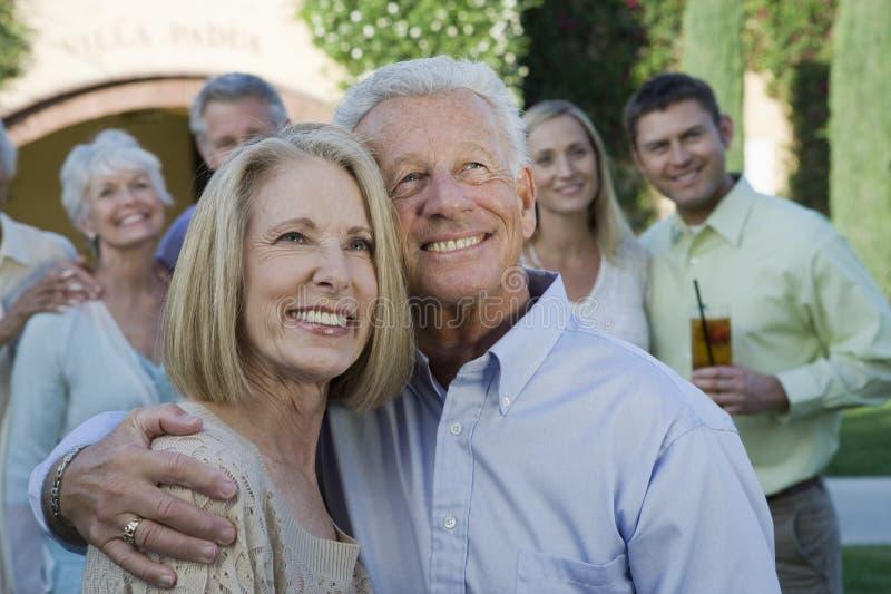 Couples supérieurs heureux se tenant ainsi que le bras autour photo stock