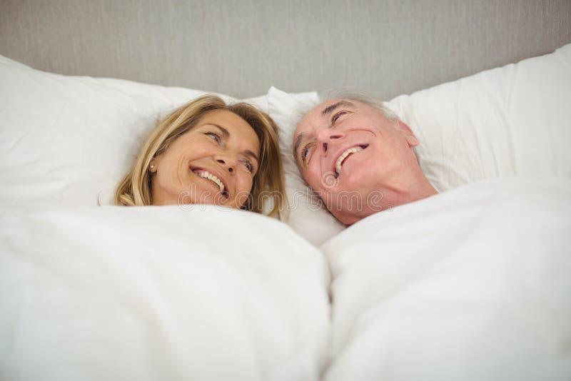 Couples supérieurs heureux se trouvant sur le lit photographie stock
