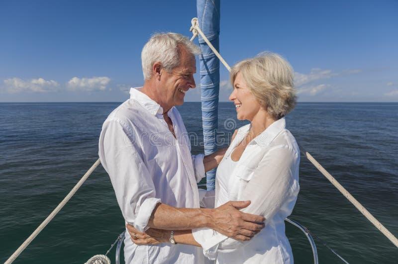Couples supérieurs heureux sur l'avant d'un bateau à voile image libre de droits