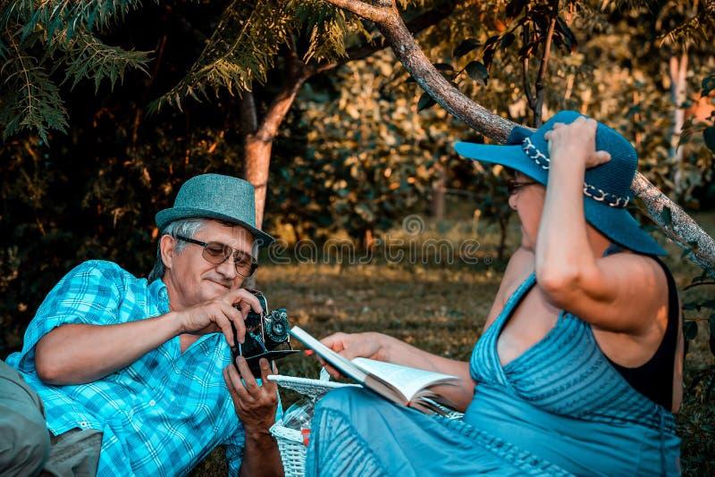 Couples supérieurs heureux sur le pique-nique prenant la photo avec la rétro caméra en parc photos libres de droits
