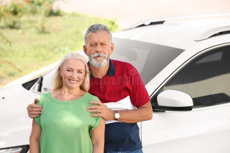 Couples supérieurs heureux tenant la voiture proche photographie stock