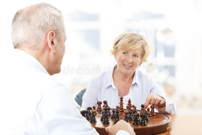 Couples supérieurs jouant des échecs ensemble photos stock