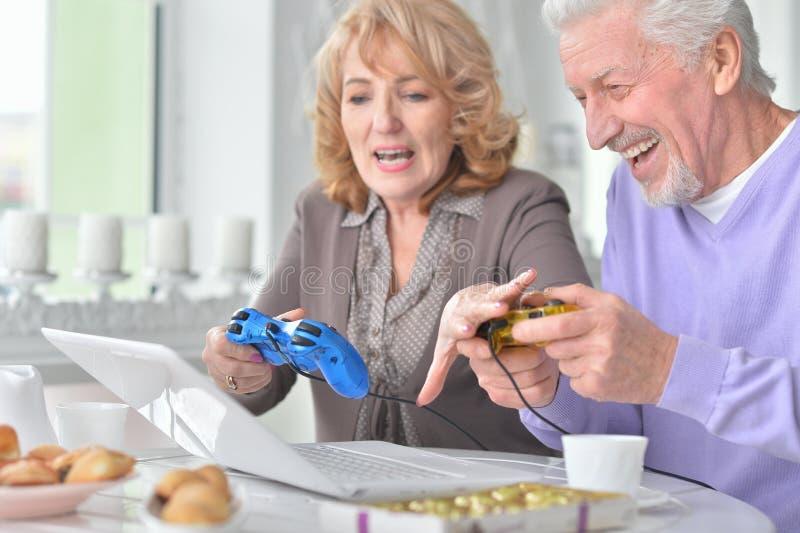 Couples supérieurs jouant le jeu d'ordinateur avec l'ordinateur portable tout en buvant t photos stock