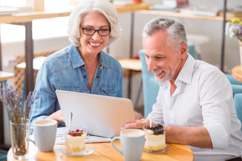 Couples supérieurs joyeux utilisant l'ordinateur portable photos libres de droits