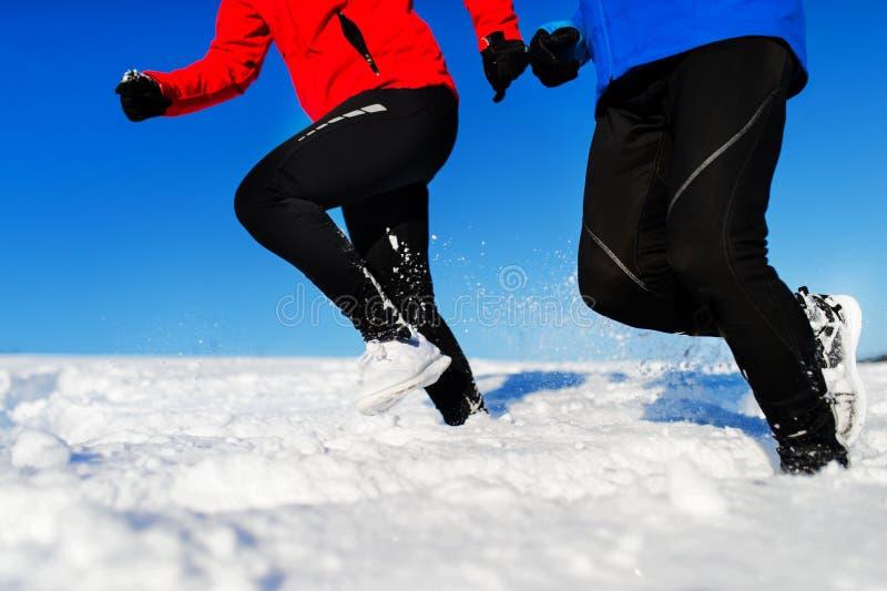 Couples supérieurs méconnaissables pulsant en nature neigeuse d'hiver photographie stock libre de droits