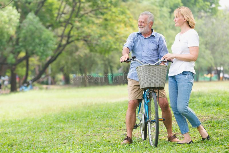 Couples supérieurs marchant leur vélo photos stock