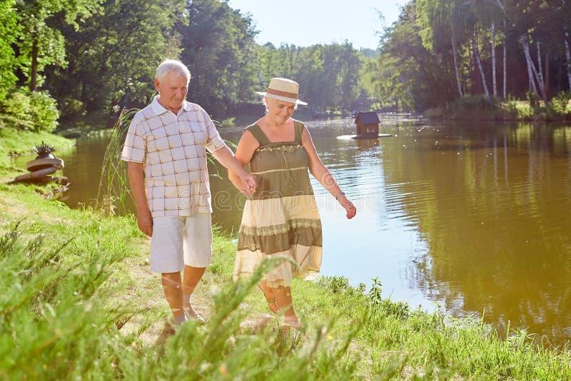 Couples supérieurs marchant près du lac photo libre de droits
