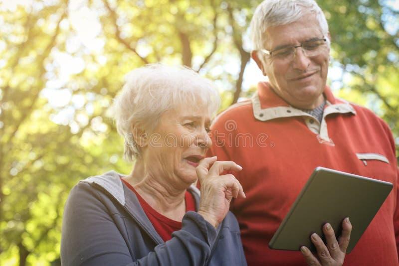 Couples supérieurs mettant en oeuvre en parc ensemble et employant le digita photos stock