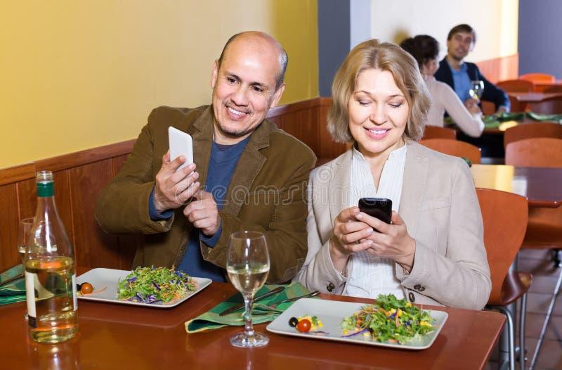 Couples supérieurs occupés avec des téléphones la date en café photographie stock