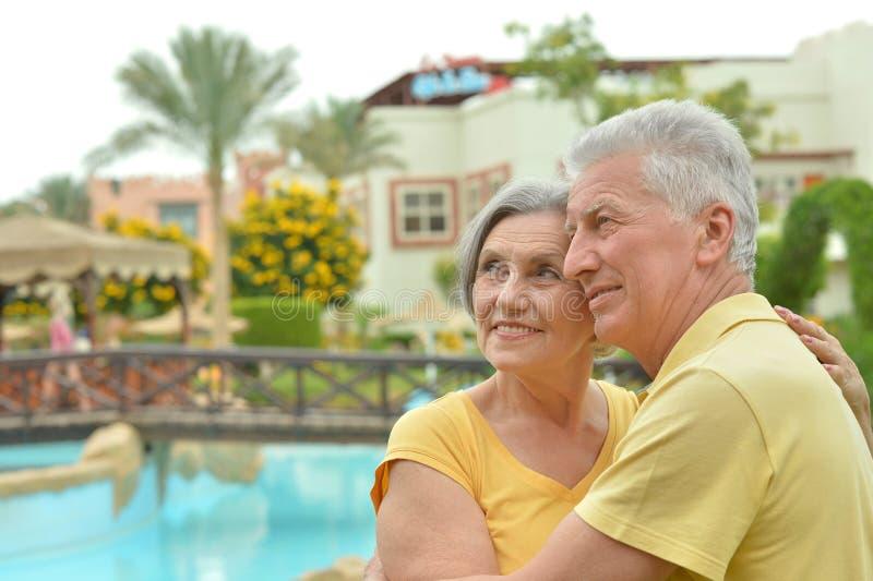 Couples supérieurs par la piscine photographie stock