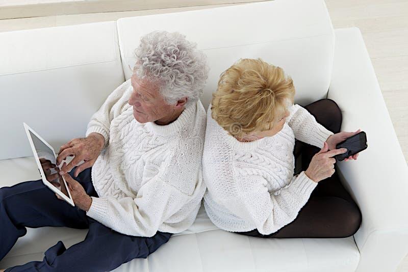 Couples supérieurs posés de nouveau à jouer arrière avec des comprimés et des iphones photo stock