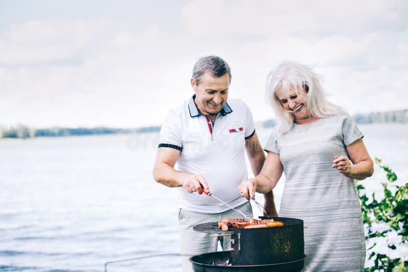 Couples supérieurs préparant des saucisses sur le barbecue photographie stock libre de droits