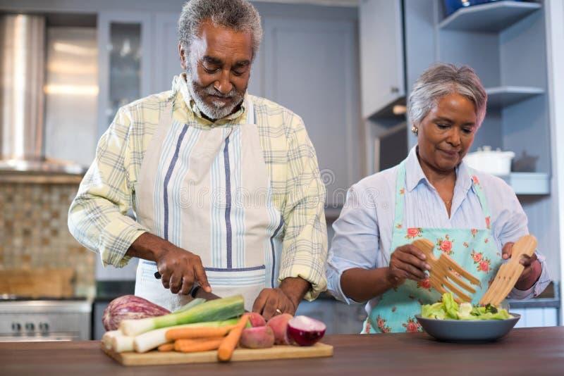 Couples supérieurs préparant la nourriture à la maison photos stock