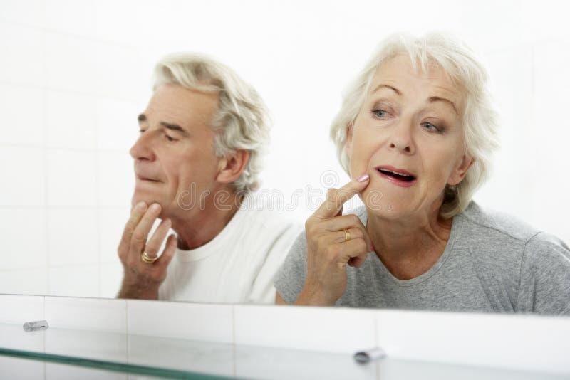 Couples supérieurs regardant des réflexions dans le miroir pour des signes du vieillissement photo libre de droits
