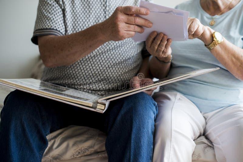 Couples supérieurs regardant l'album photos de famille image stock