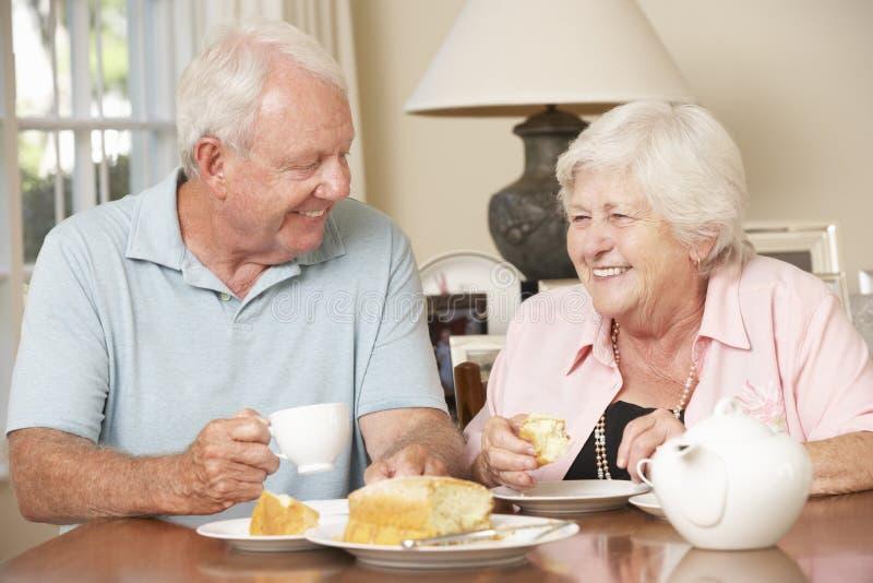 Couples supérieurs retirés appréciant le thé d'après-midi ensemble à la maison photo libre de droits
