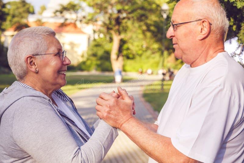 Couples supérieurs romantiques appréciant la promenade en parc photo stock