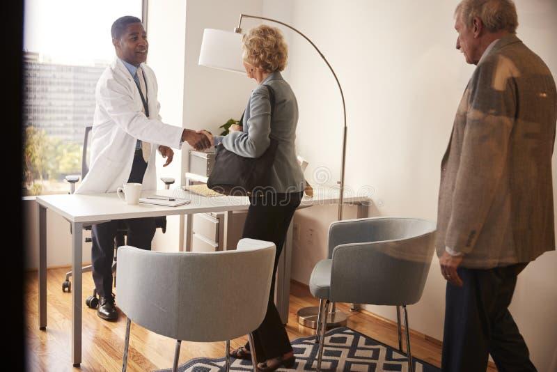 Couples supérieurs salué par la visite masculine de docteur With Handshake On à l'hôpital pour la consultation photo stock