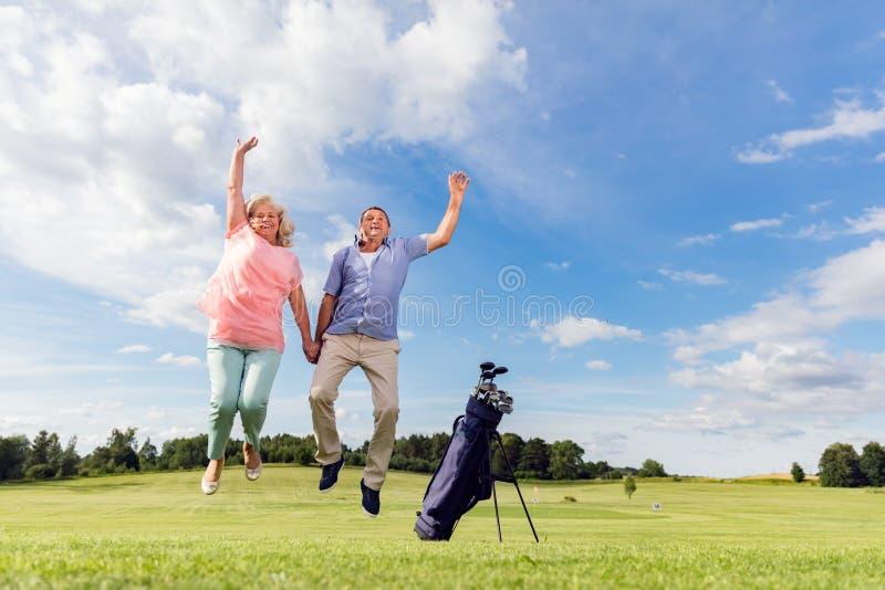 Couples supérieurs sautant sur un terrain de golf images libres de droits