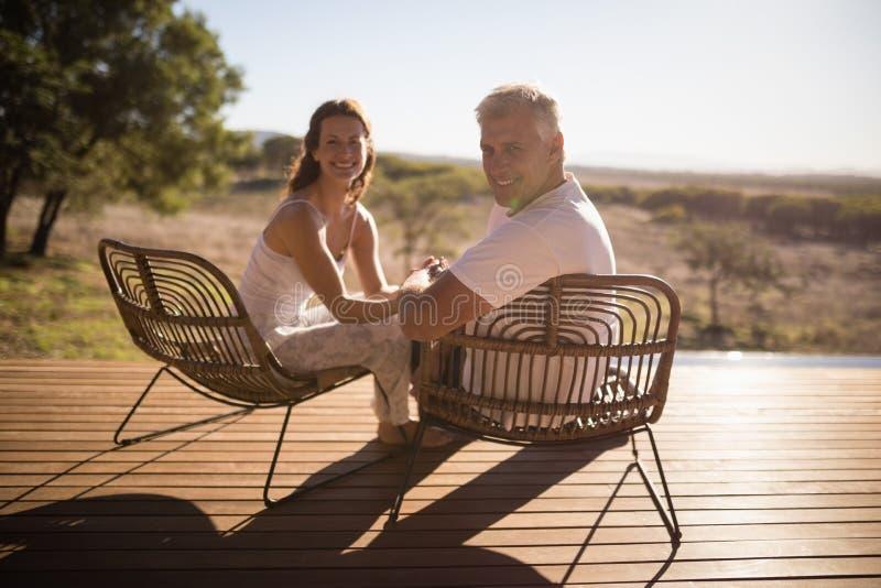 Couples supérieurs se reposant sur des chaises à la station de vacances images libres de droits