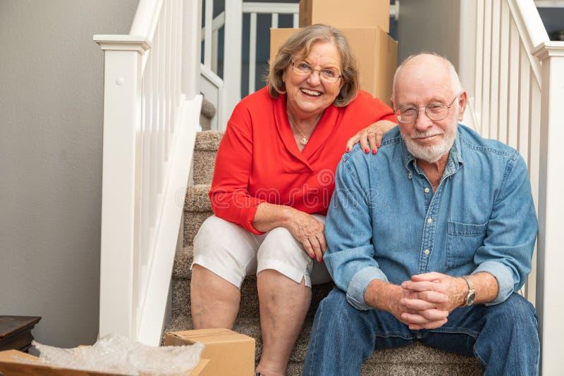 Couples supérieurs se reposant sur des escaliers entourés en déplaçant des boîtes photo libre de droits