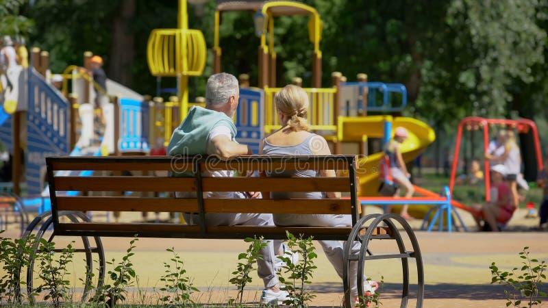 Couples supérieurs se reposant sur le banc près du terrain de jeu, jouer de observation de petits-enfants image libre de droits