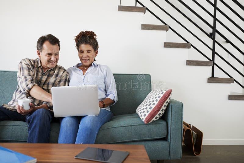 Couples supérieurs se reposant sur Sofa At Home Using Laptop ensemble image stock