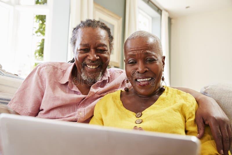 Couples supérieurs se reposant sur Sofa Using Laptop At Home ensemble image stock