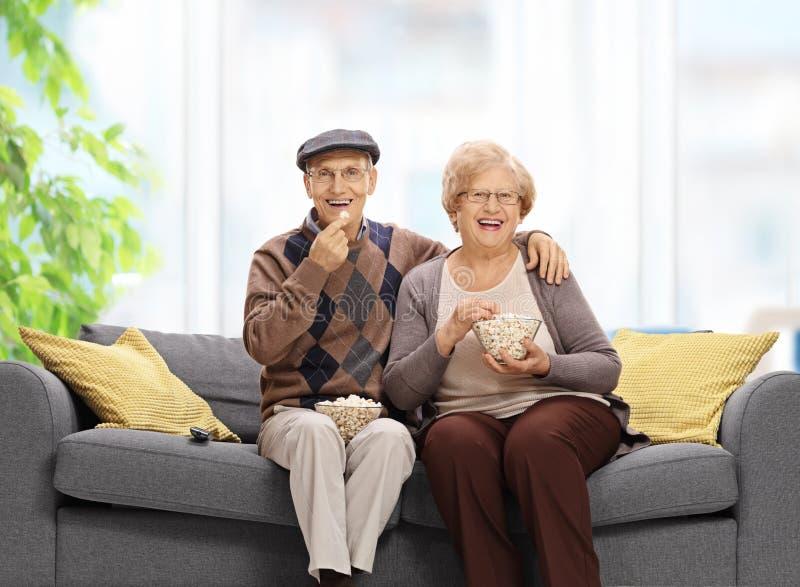 Couples supérieurs se reposant sur un sofa et mangeant du maïs éclaté photos stock
