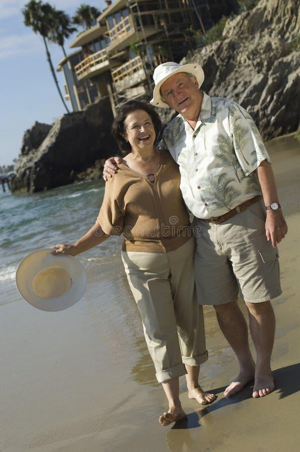 Couples supérieurs se tenant à la plage photographie stock