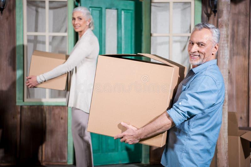 Couples supérieurs se tenant sur le porche de la nouvelle maison avec des boîtes en carton et regardant l'appareil-photo images libres de droits