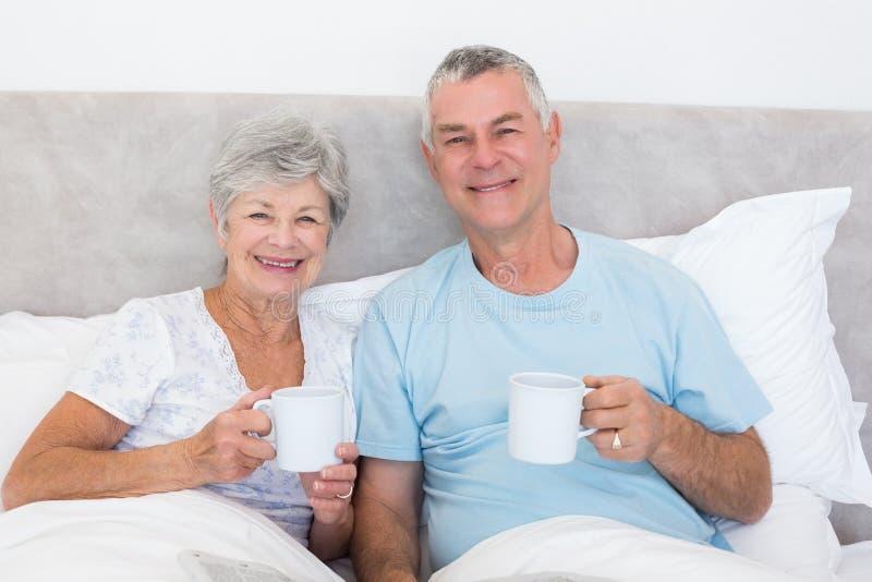 Couples supérieurs tenant des tasses de café dans le lit photo stock