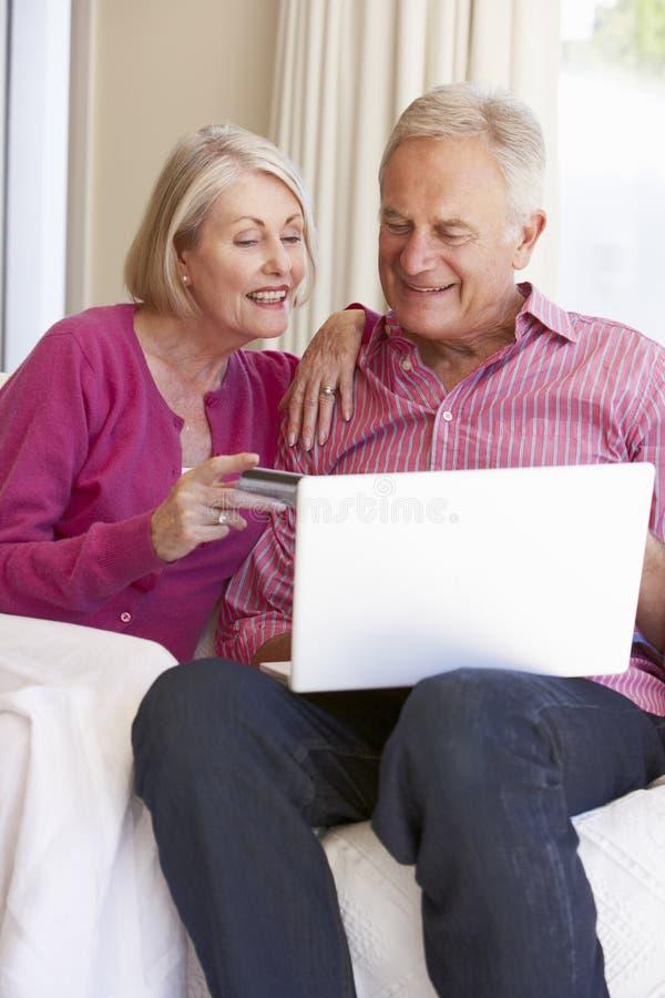 Couples supérieurs utilisant l'ordinateur portable pour l'achat en ligne à la maison photo stock