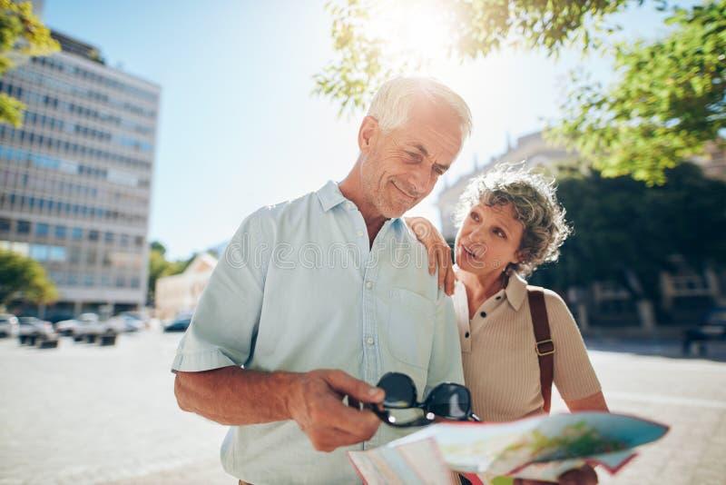 Couples supérieurs utilisant la carte de route dans une ville étrangère images libres de droits