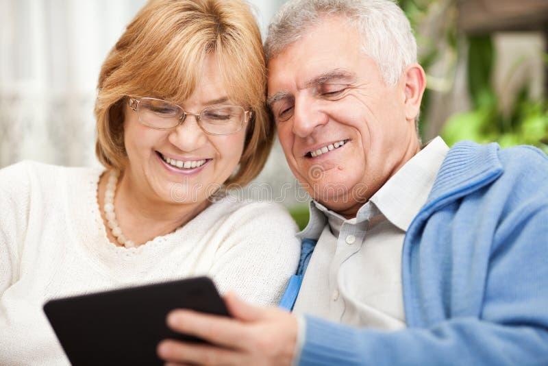 Couples supérieurs utilisant la tablette photos libres de droits